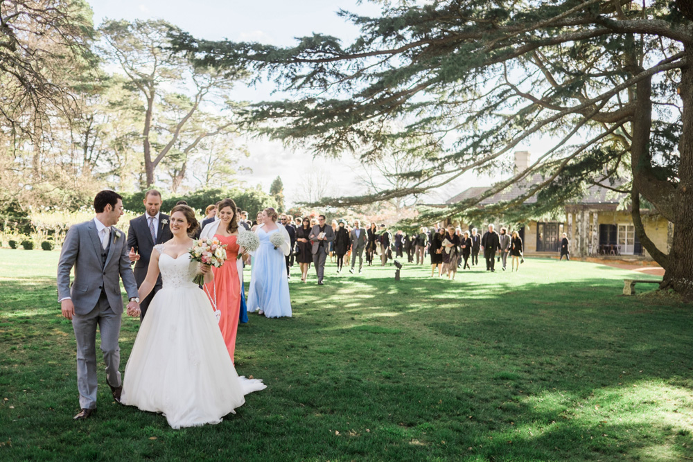 Alice & Rob's guests follow them in a procession across the lawn. Photo: James Day