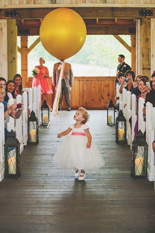 Flower girl carrying balloon down the aisle
