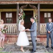 Bride and groom with wedding party infront of old country house