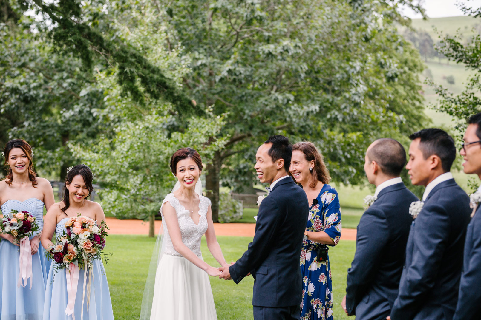 Bride and Groom being married in garden with wedding party and marrige celebrant